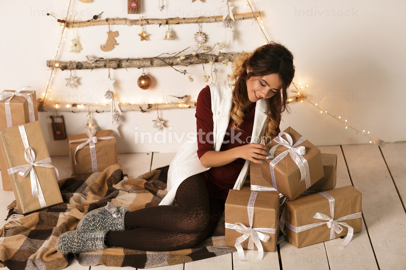 Cheerful beautiful woman open the Christmas present over white backgound. New Year 2020.