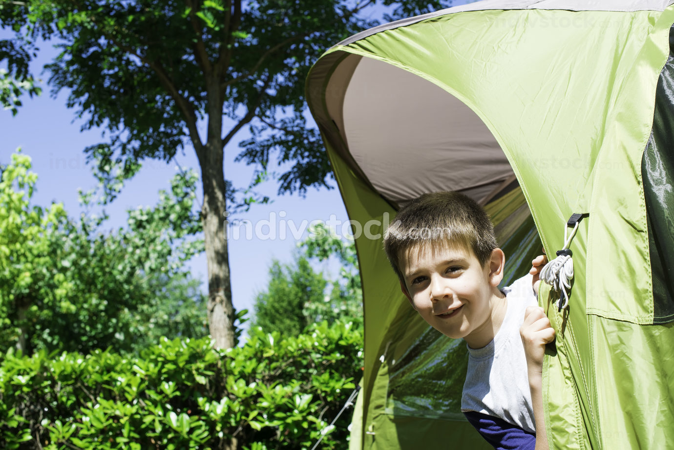 Child peeks from a tent