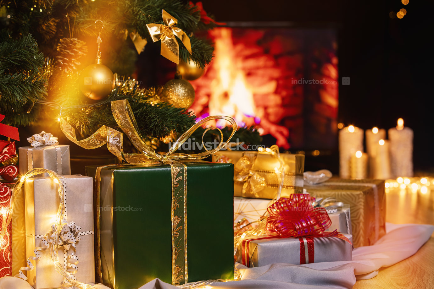 Christmas presents and candles under Christmas tree
