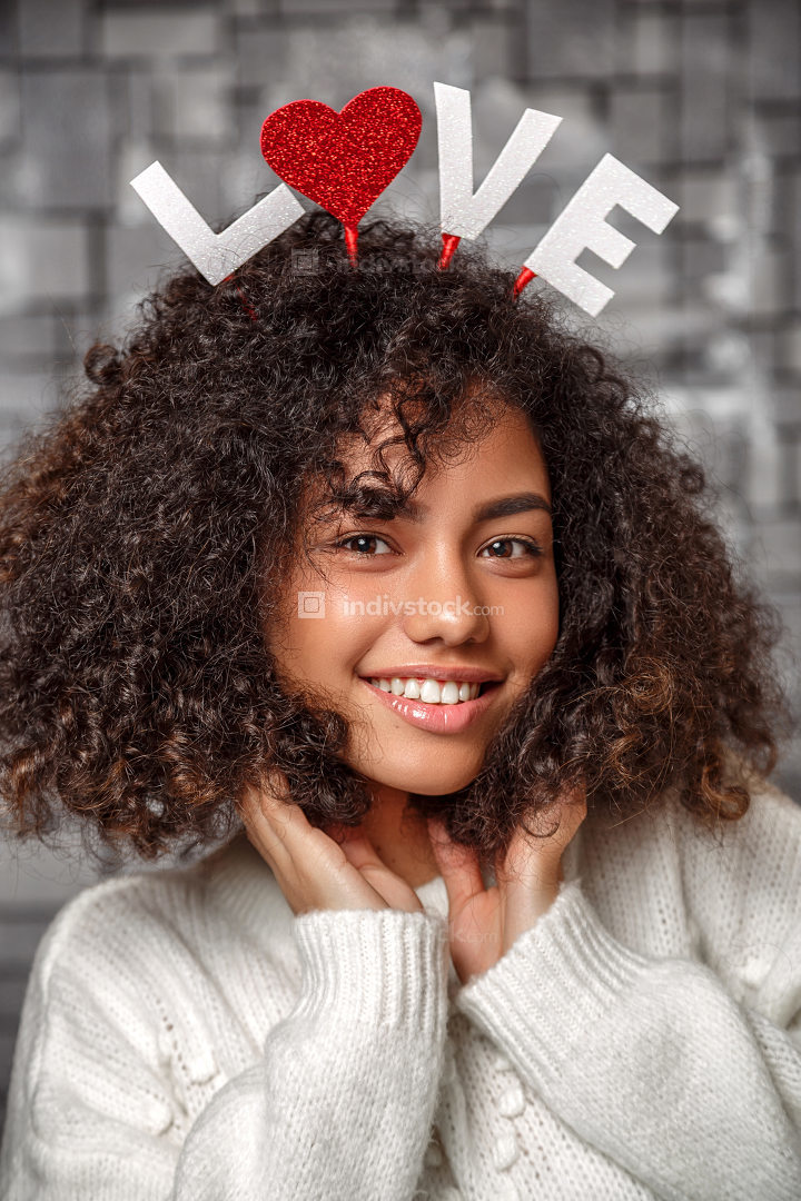 close-up portrait of a young beautiful curly-haired girl with a rim with the inscription love on her head. the girl posing and smiling at the camera.