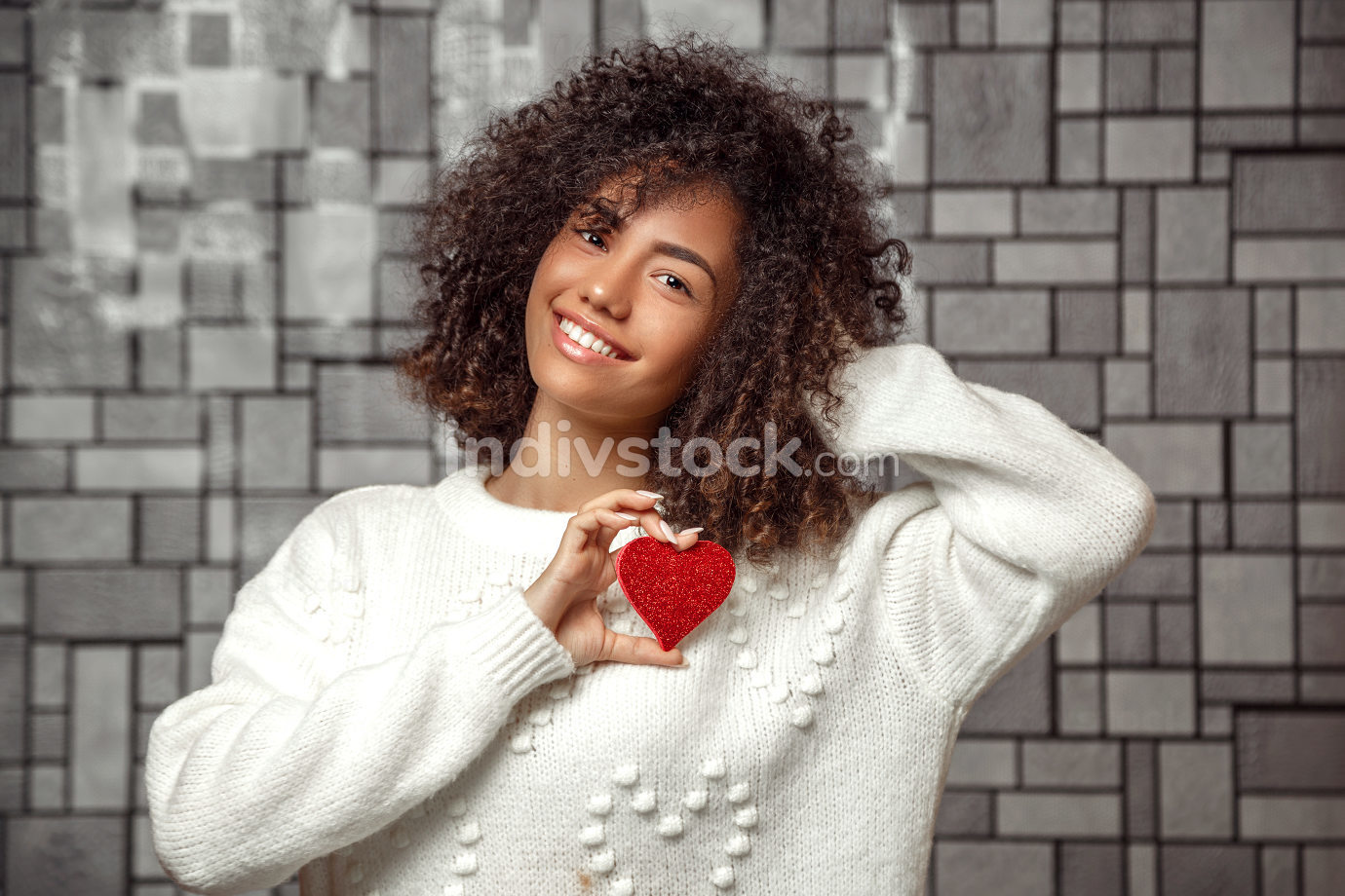 close-up portrait of a young curly-haired African American girl in a white sweater holding a paper heart .  shallow depth of focus