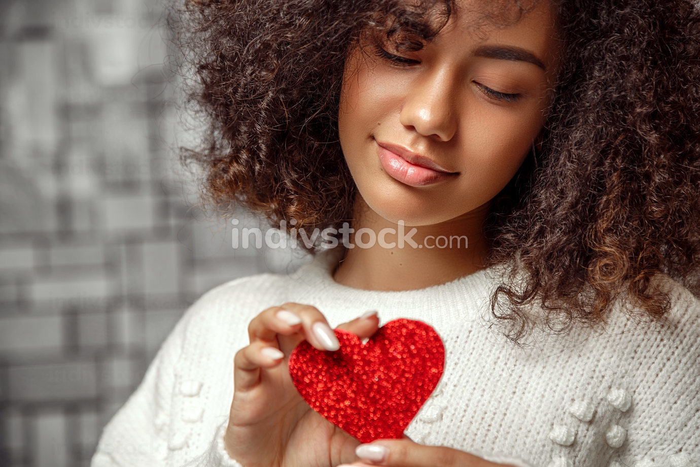 close-up portrait of a young curly-haired African American girl in a white sweater holding a paper heart . face focus, shallow depth of focus