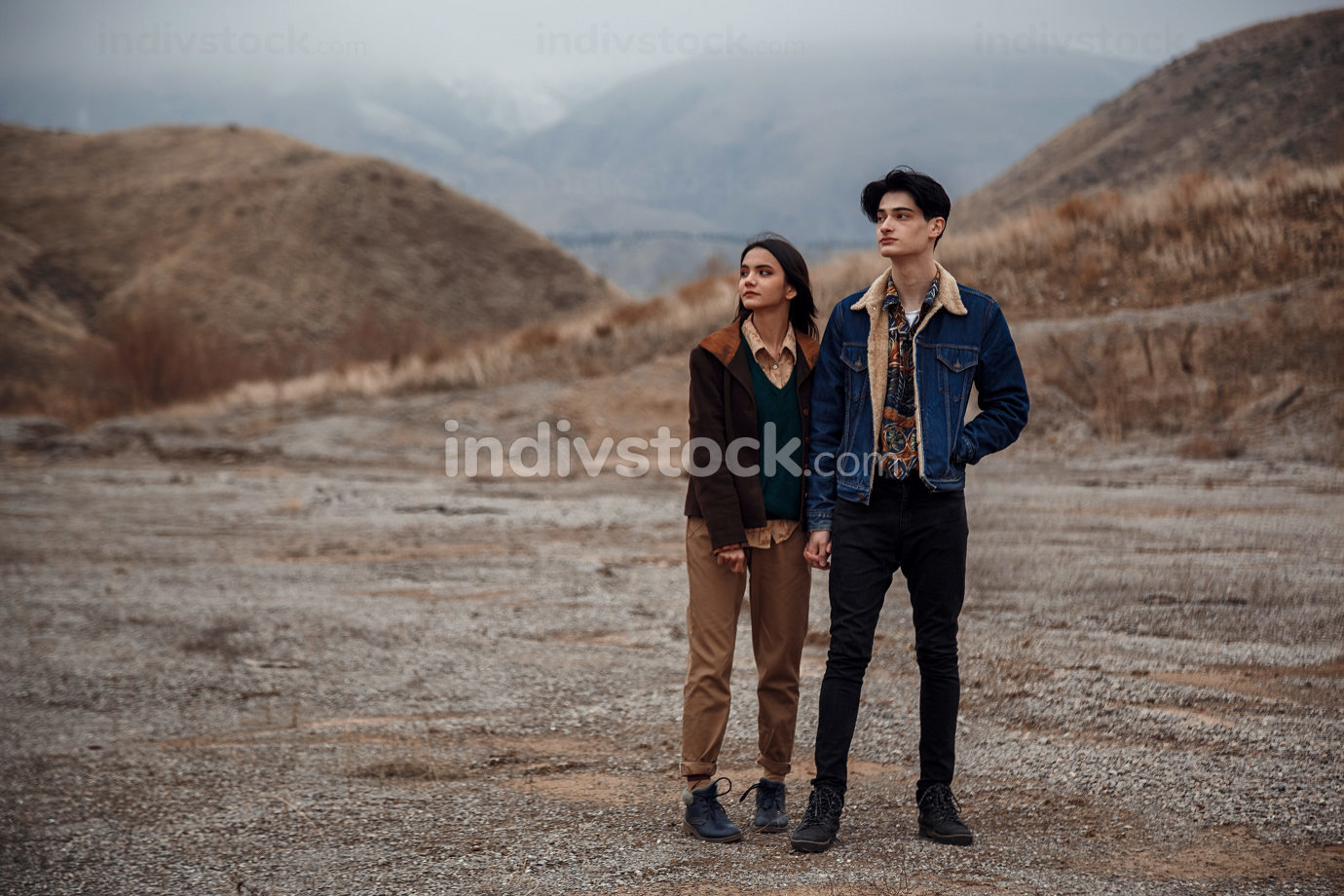 Dramatic portrait of a young brunette girl and a guy in cloudy weather. selective focus, small focus area