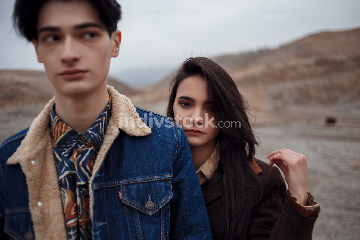 Dramatic portrait of a young brunette girl and a guy in cloudy weather. she