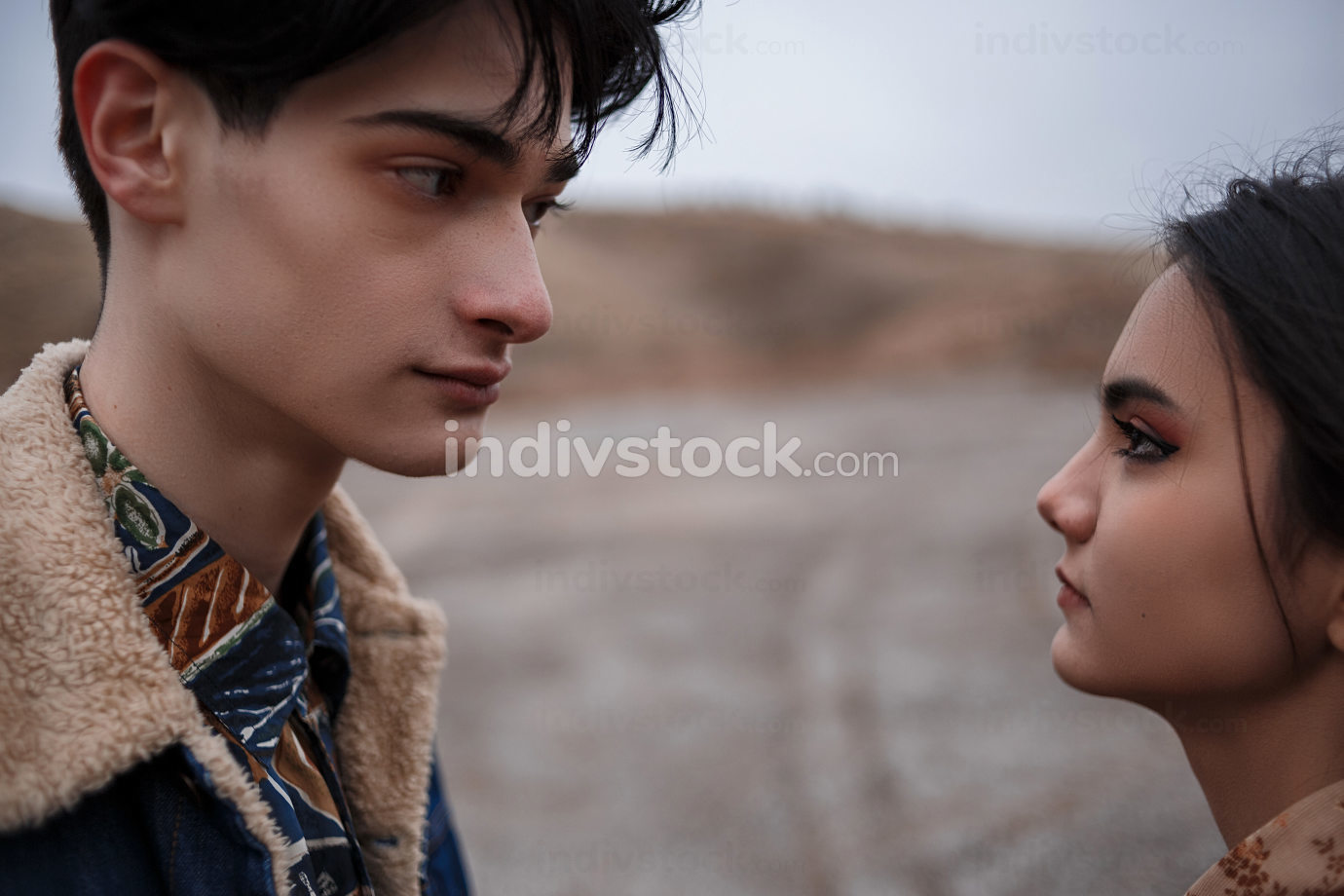 Dramatic portrait of a young brunette girl and a guy in cloudy weather.they look into each other