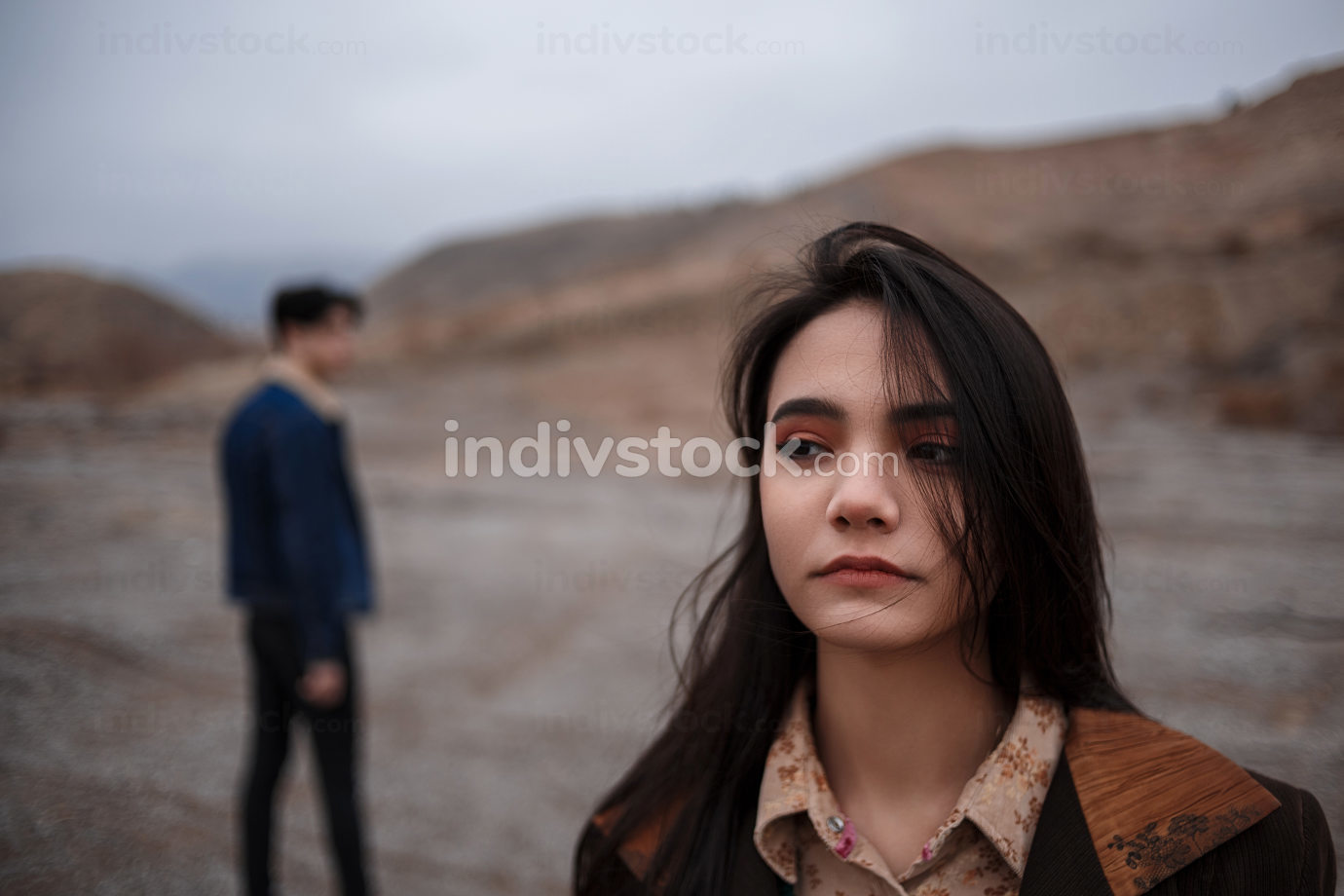 Dramatic portrait of a young brunette girl in cloudy weather. somewhere behind her, out of focus, her young lover boyfriend leaves her after break up . selective focus, small focus area
