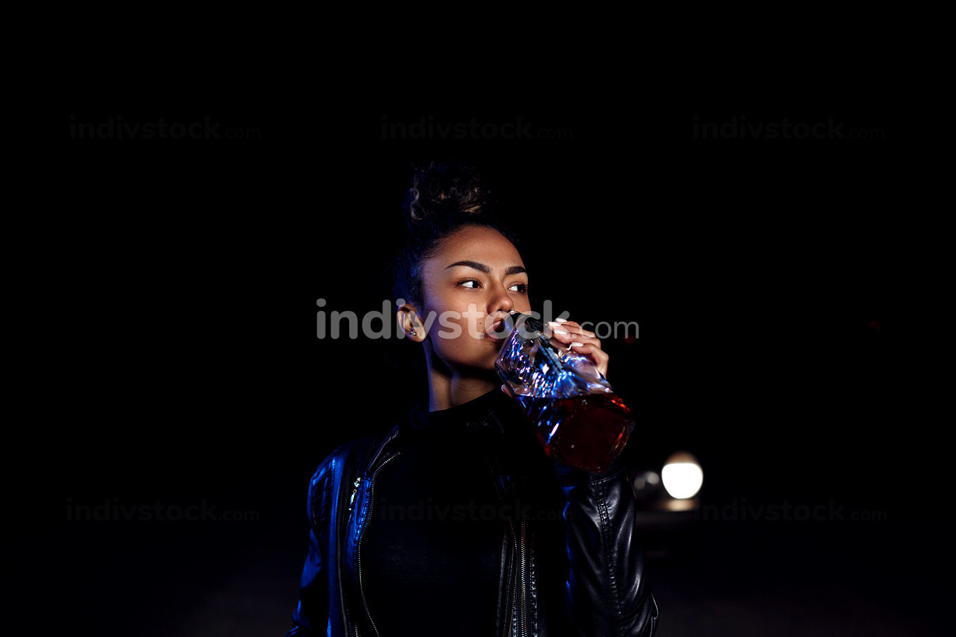 drunk young African American mulatto girl in a leather jacket and black clothes