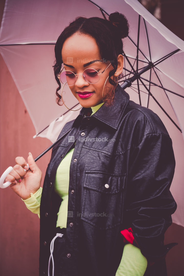 Fashionable young woman holding a pink umbrella