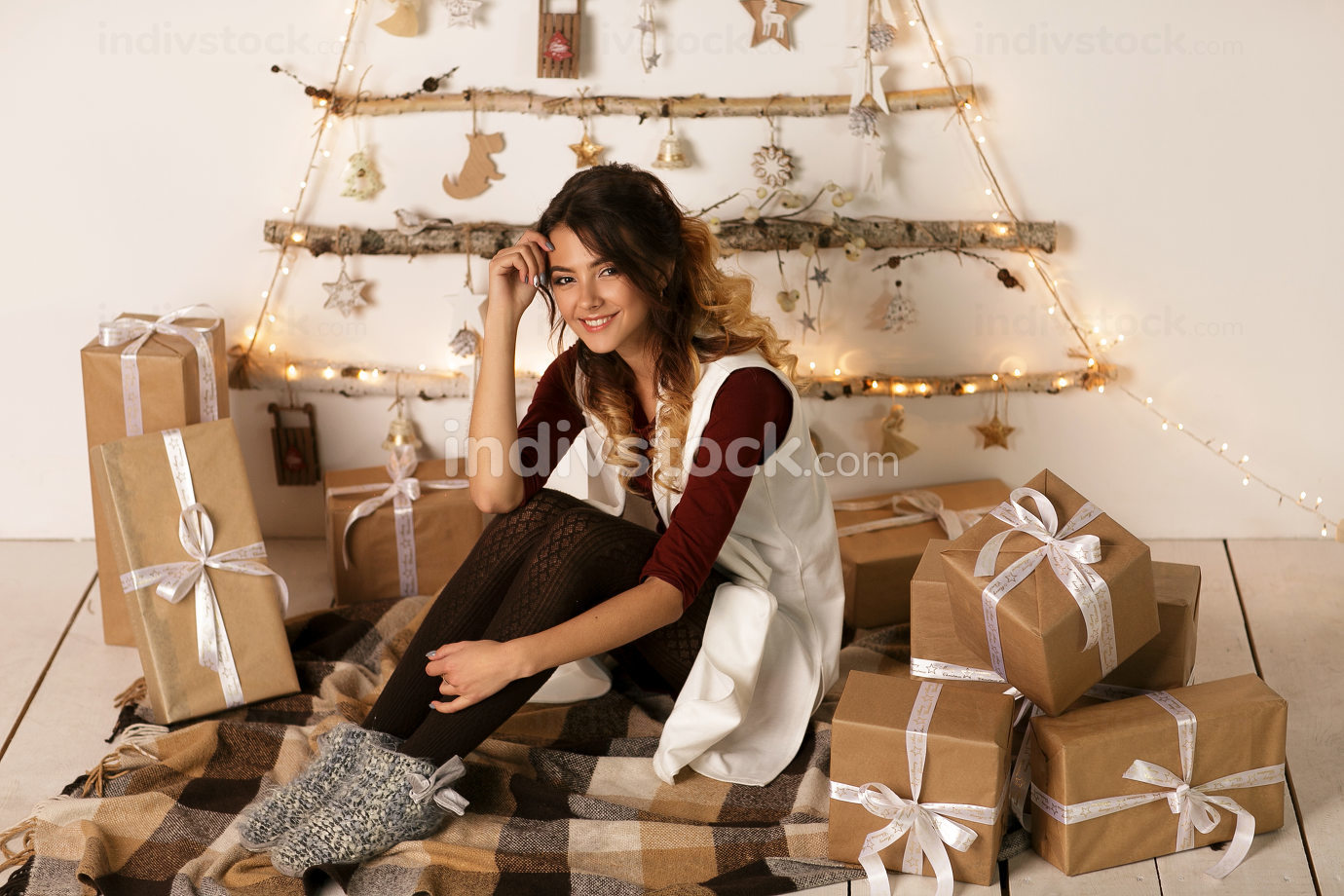 Happy excited woman sitting near the rustic Christmas tree with many Christmas gifts