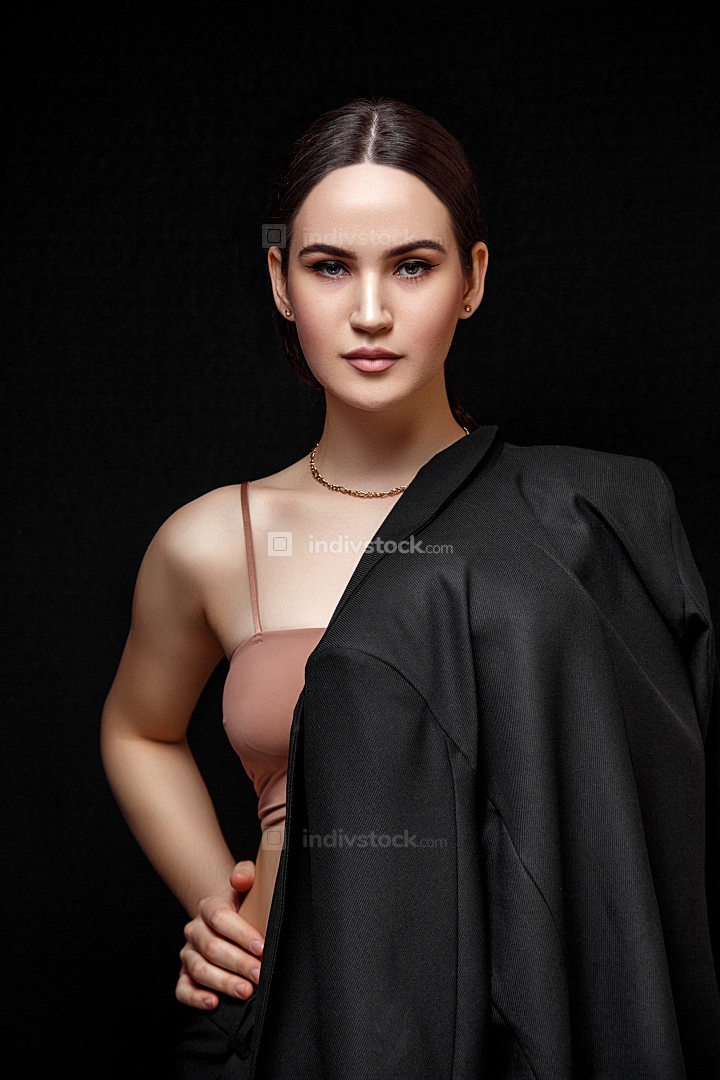 High fashion portrait of young elegant woman in black suit and b
