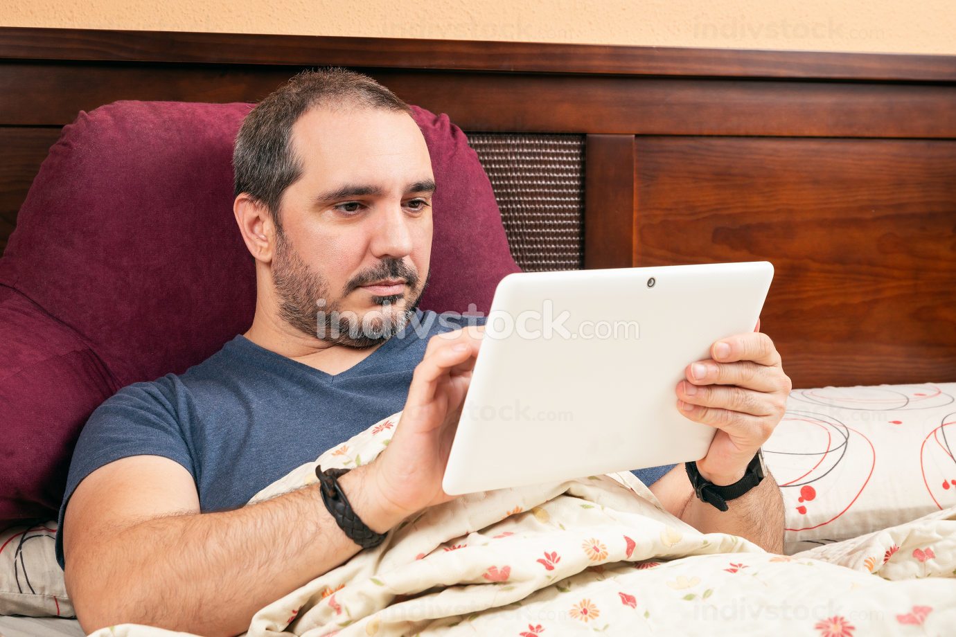 ill man using tablet in the bed.