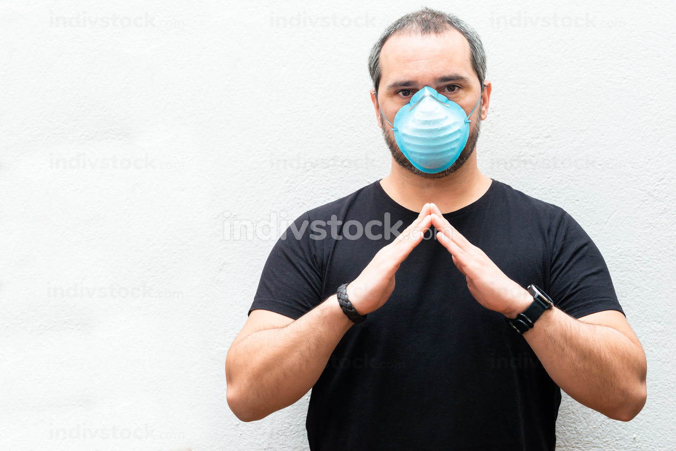 Man with medical mask holds hands over a house. Concept of home stay, quarantine.