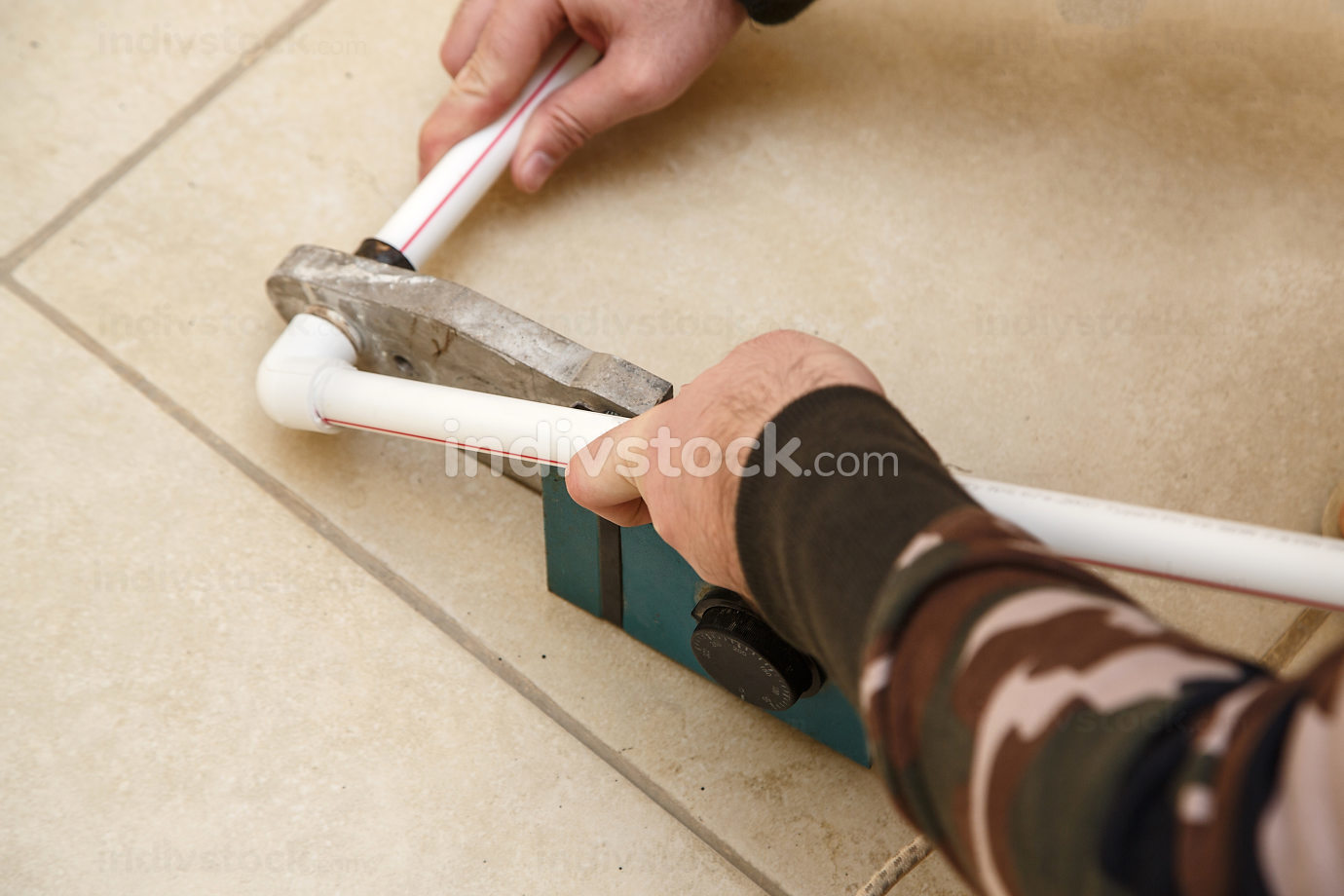 men's hands connect plastic pipes with an iron