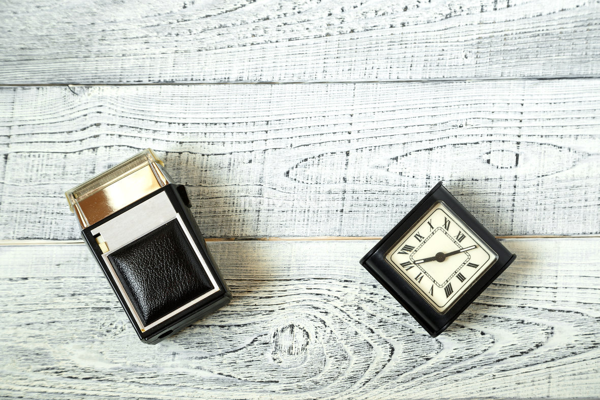 morning. vintage electric shaver and retro alarm clock on shabby