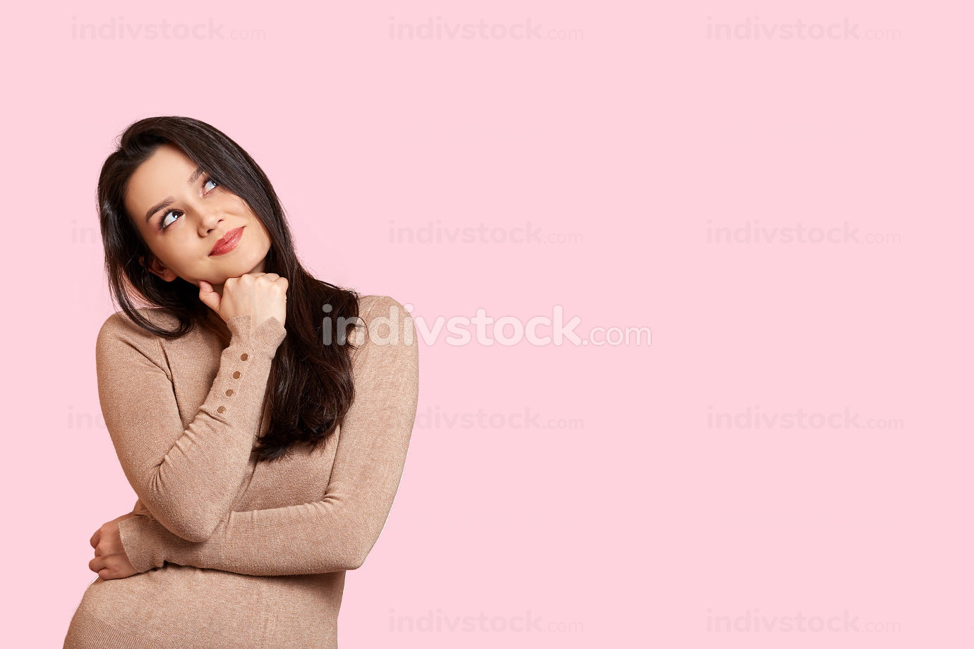 portrait of a thoughtful young beautiful girl in a light brown jacket on a pink isolated background