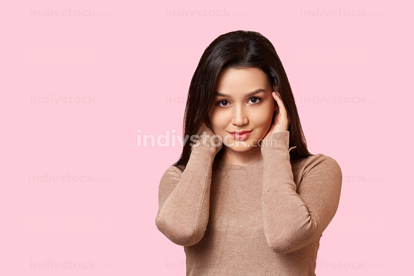 portrait of a young beautiful Asian brunette girl in a light brown jacket holding her hands over her face . on a pink isolated background with copyspace