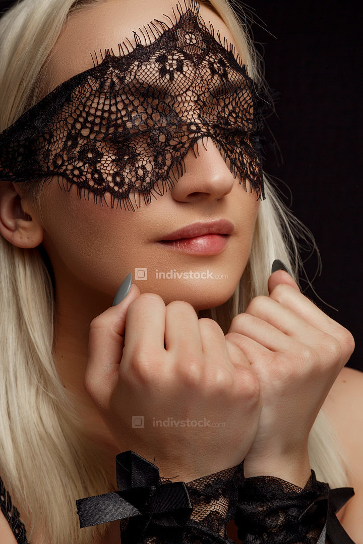 portrait of a young beautiful blonde woman in a lace face mask and lace handcuffs on a black isolated background