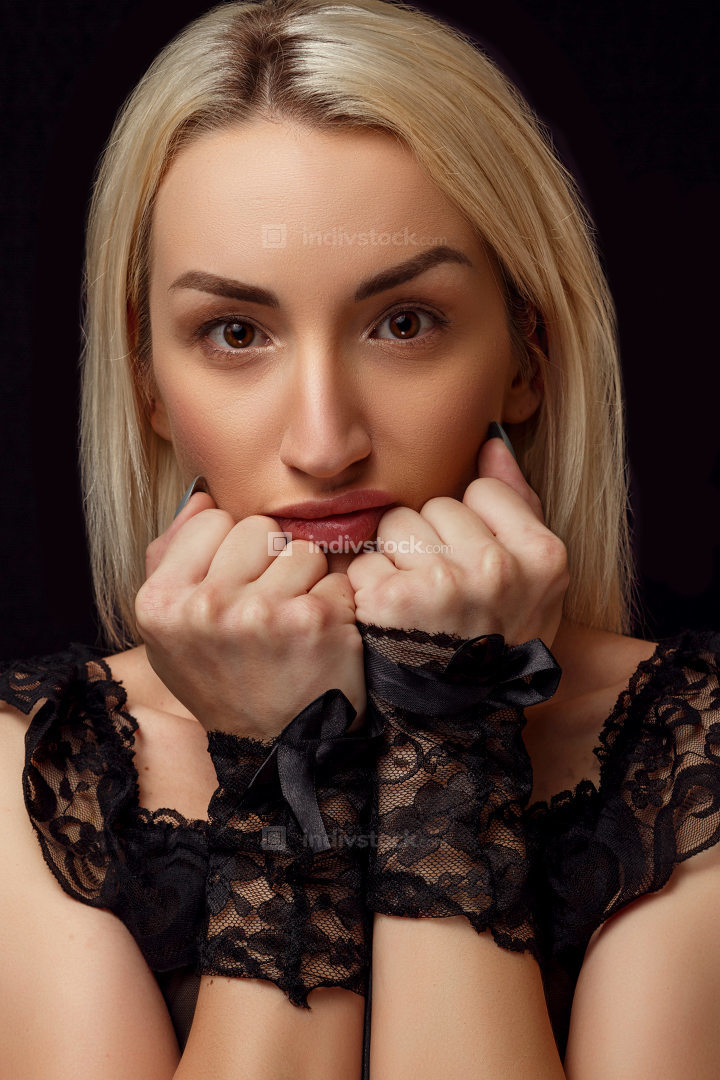 portrait of a young beautiful blonde woman in lace handcuffs on a black isolated background