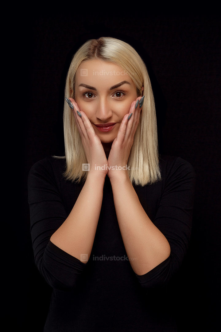 portrait of a young beautiful blonde woman with hands on her face in black clothes on a black isolated background