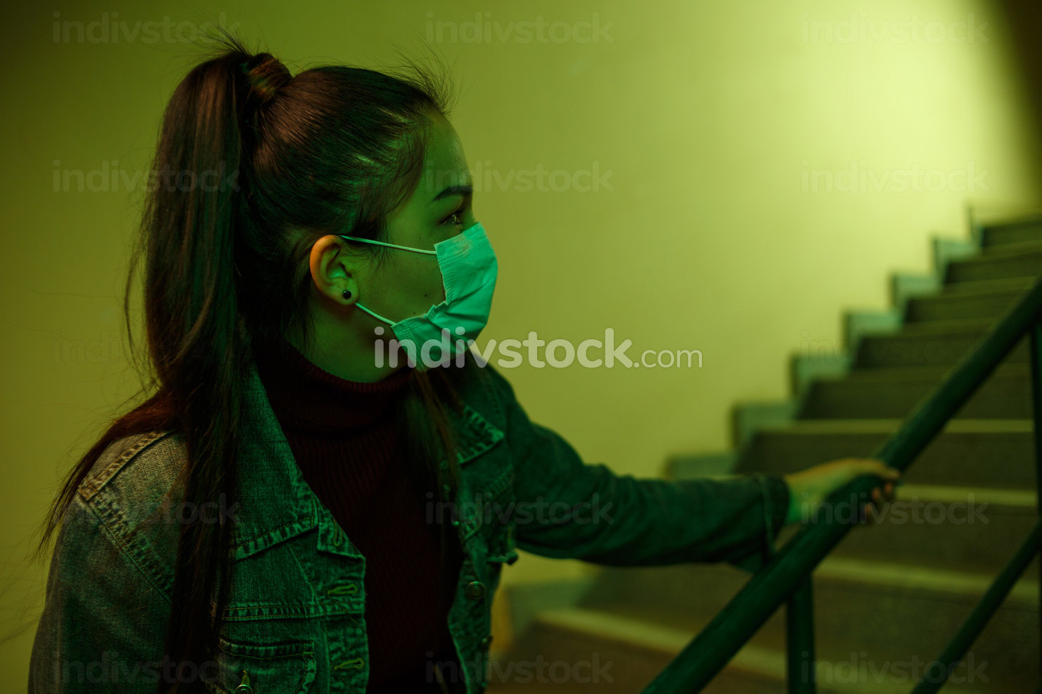 portrait of an Asian girl in a disposable medical mask. stairwell of the hospital. the girl looks back anxiously. fear