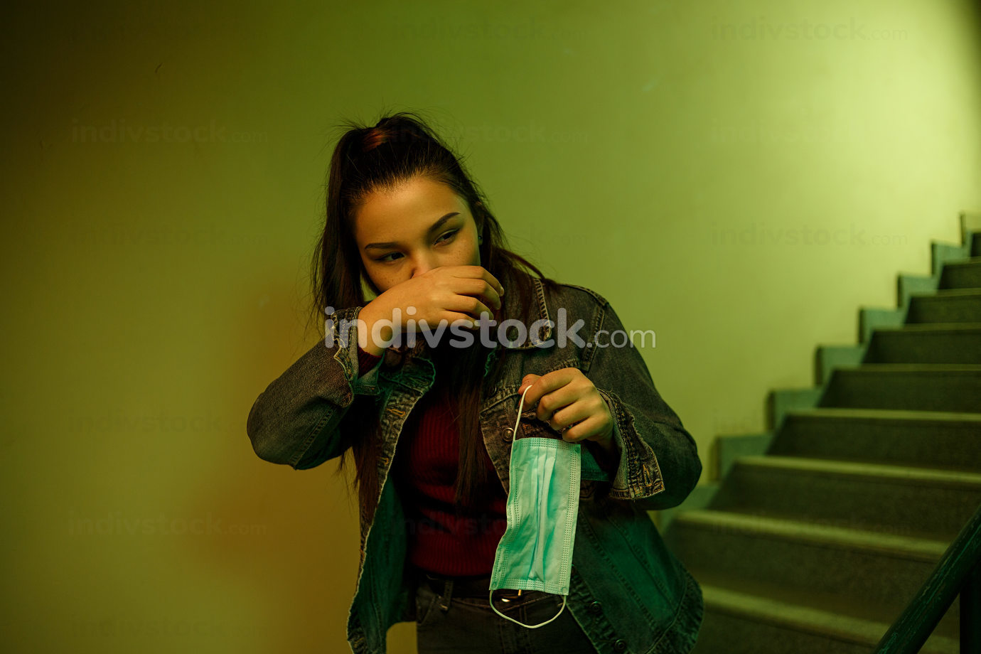 portrait of an Asian young woman in a disposable medical mask. stairwell of the hospital. the girl feels symptoms of infection with the virus
