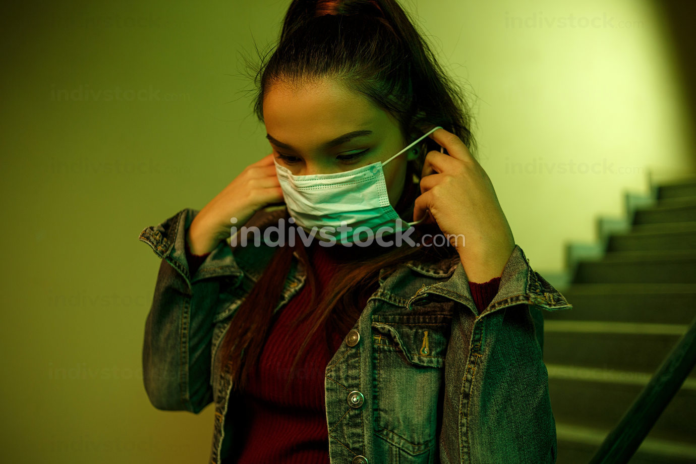 portrait of an Asian young woman. stairwell of the hospital. the girl wears a mask to avoid getting infected with the virus