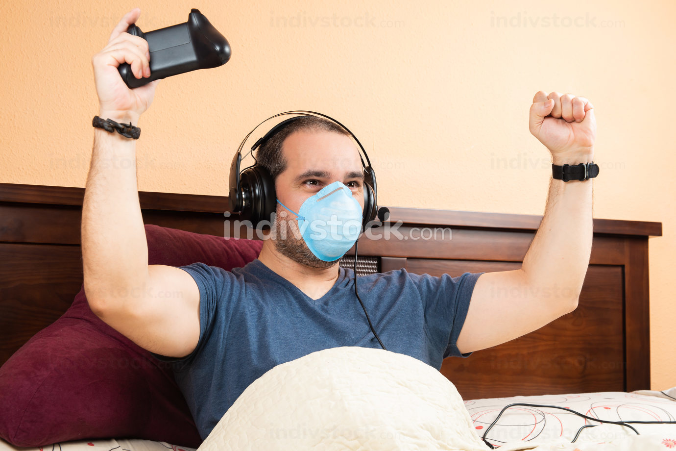 sick man with headphone and medical mask, playing videogames in