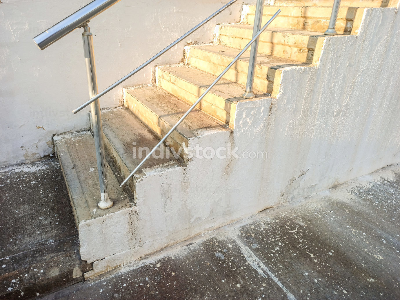 white cement street stairs with metal handrails