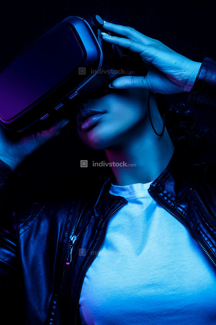 Young african american girl playing game using VR glasses, enjoying 360 degree virtual reality headset for gaming, isolated on black background in neon light