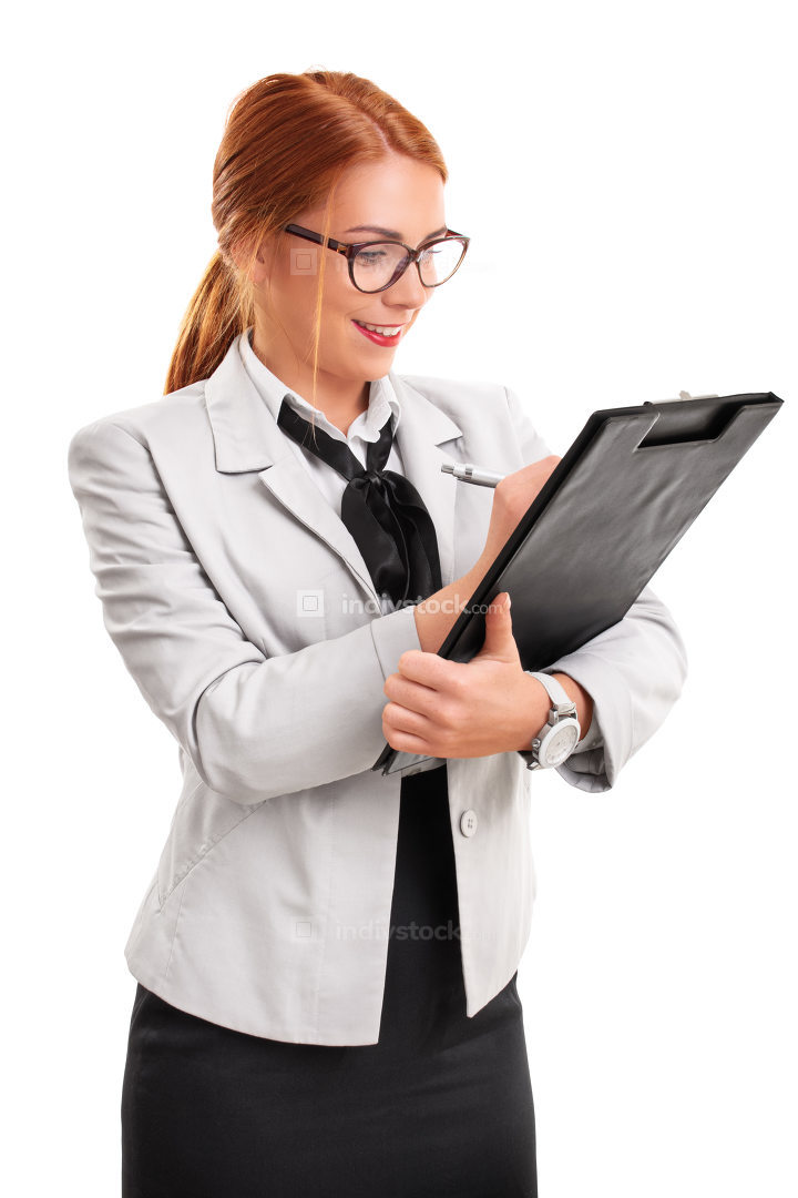 Young fashionable businesswoman writing on a clipboard