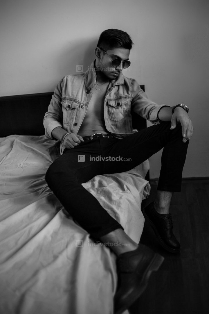 young stylish guy in denim jacket on the bed