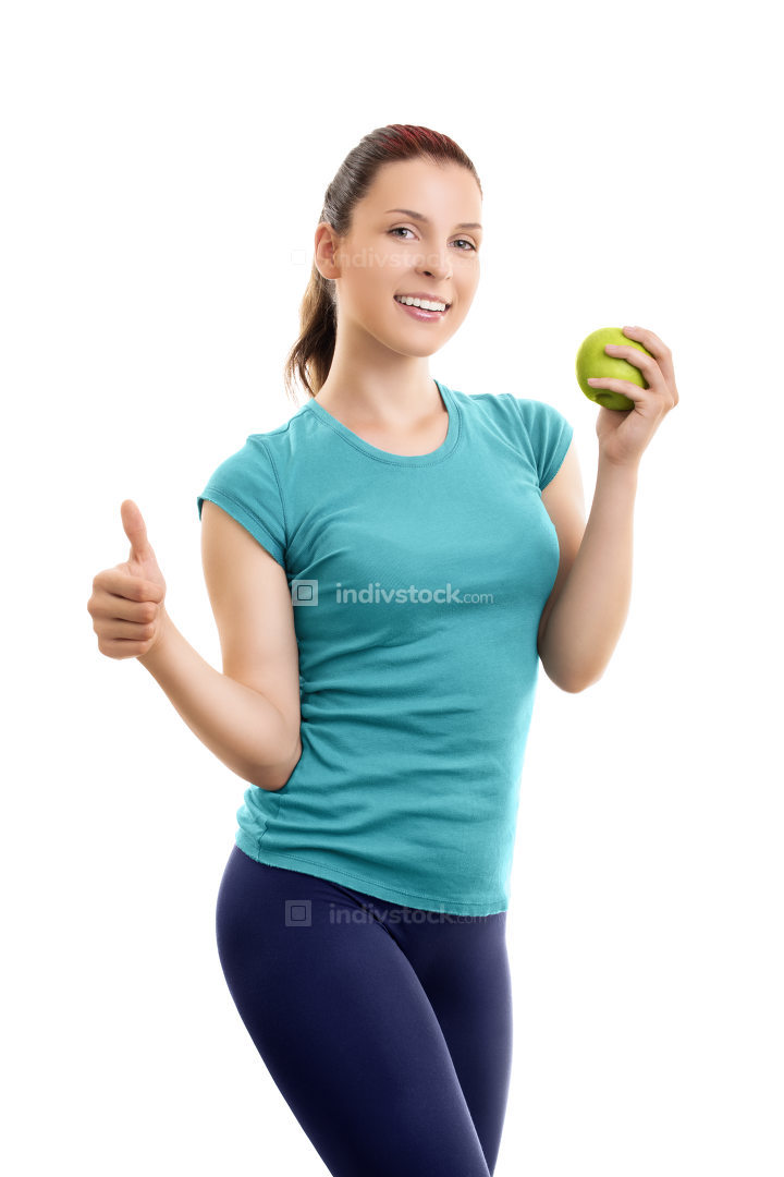 Young woman holding green apple and giving thumb up