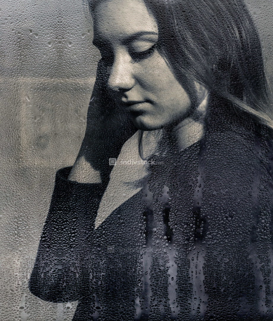 Young woman viewed through moisture on a window