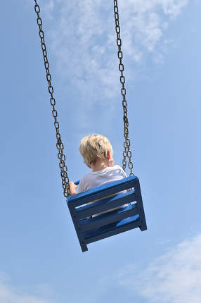 A Boy With Cochlear Implants Riding Swing in Park