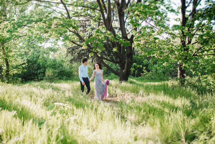 a guy and a girl walk in the spring garden of lilacs