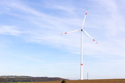 A windmill on a field with blue sky