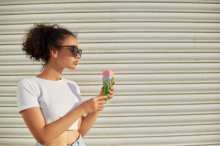 a young beautiful African-American girl in a white t-shirt and light jeans eats ice cream against a light wall on a Sunny day.