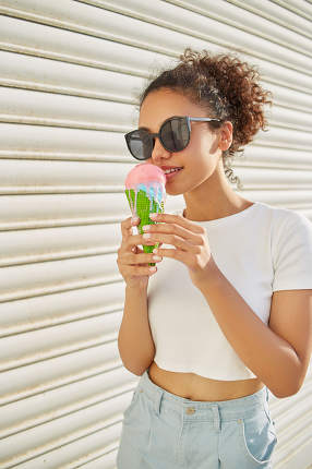 a young beautiful African-American girl in a white t-shirt and light jeans eats ice cream on a Sunny day. selective focusing. small focus area
