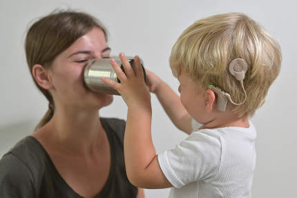 Boy with Cochlear Implants Playing Tin Can Phone