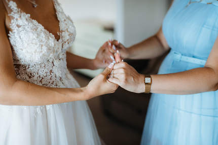 bride holds mom's hands