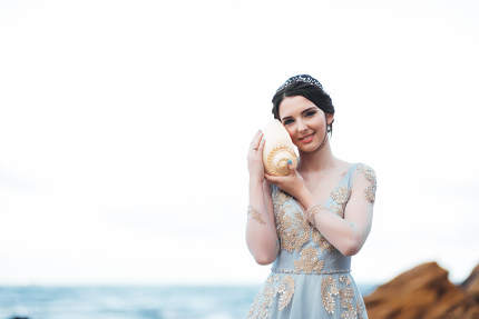 bride with a big shell on the beach