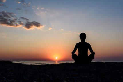 girl on the beach at dawn in yoga assana