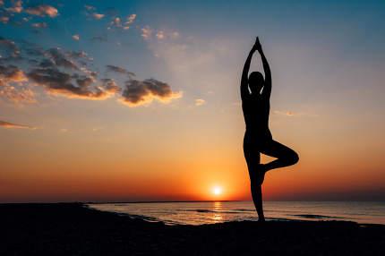 girl on the beach in yoga assana