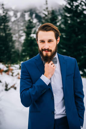 groom in a blue suit in the mountains Carpathians