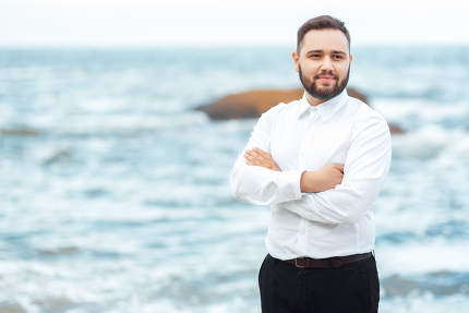 groom in a white shirt and black pants by the ocean