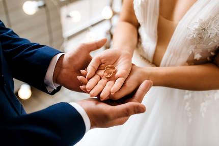 groom puts bride on wedding ring