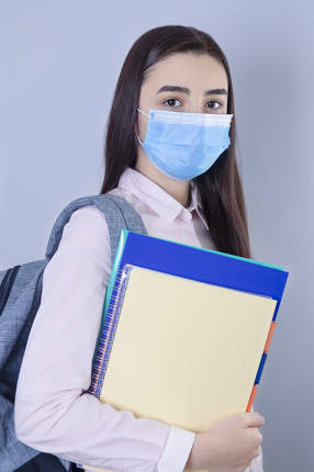 High school girl with mask on her face going back to school