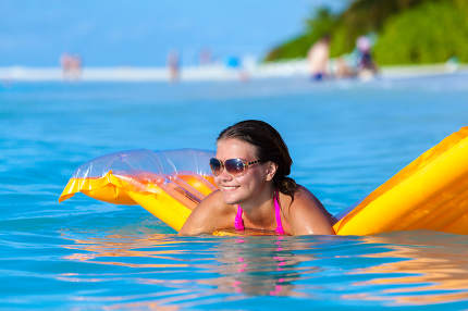 Maldives, a young woman in the water on an air mattress
