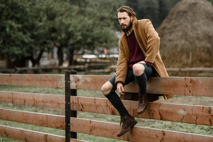 man in a brown coat on a wooden fence