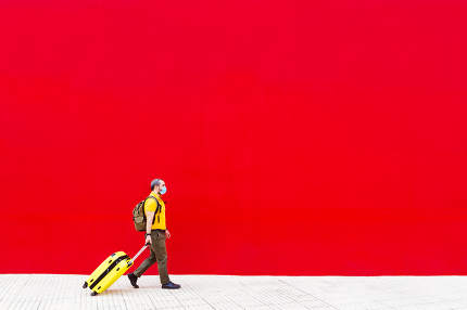 man with yellow suitcase and medical mask walking down the street